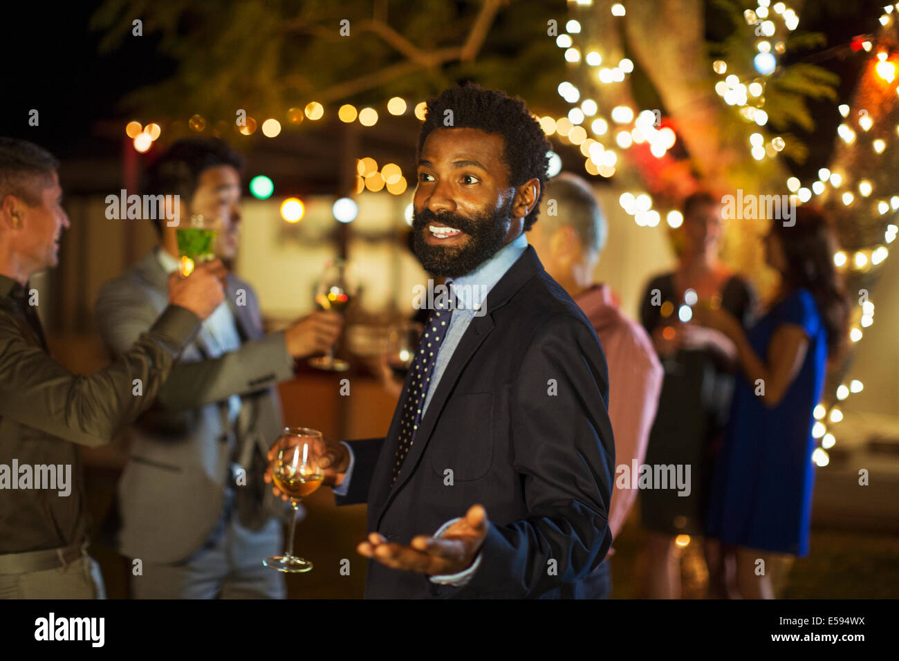 Man gesturing avec wine at party Photo Stock