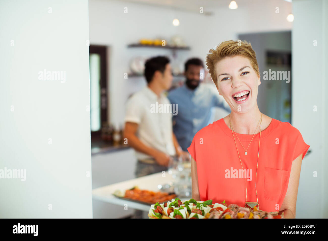 Woman carrying tray of food at party Photo Stock
