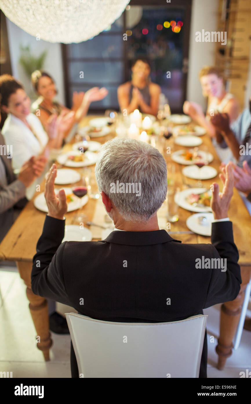 Les amis applaudir at dinner party Photo Stock