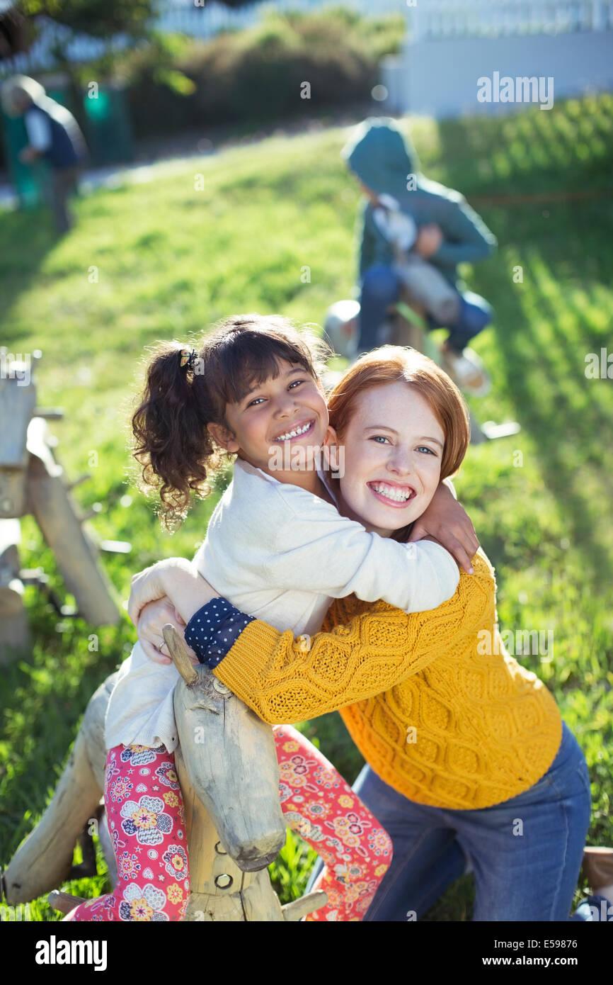 Élève et l'enseignant hugging outdoors Photo Stock