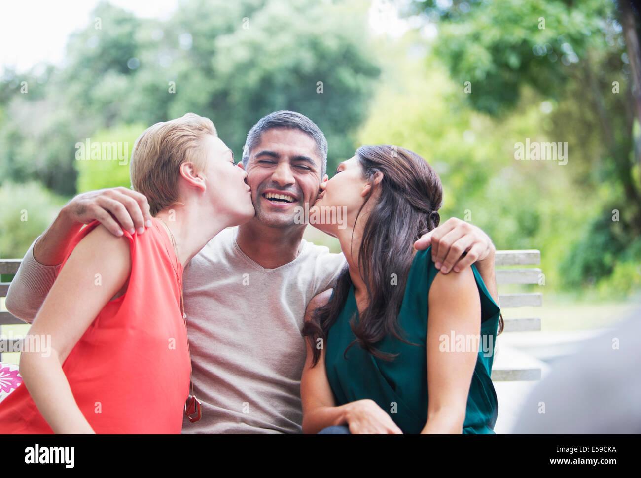 Les femmes s'embrasser les joues de l'homme à l'extérieur Photo Stock