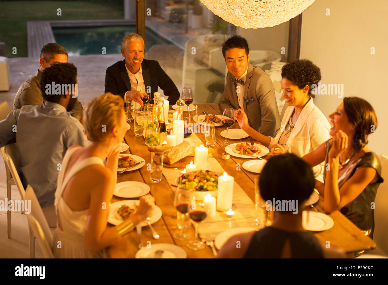 Les amis manger ensemble at dinner party Photo Stock