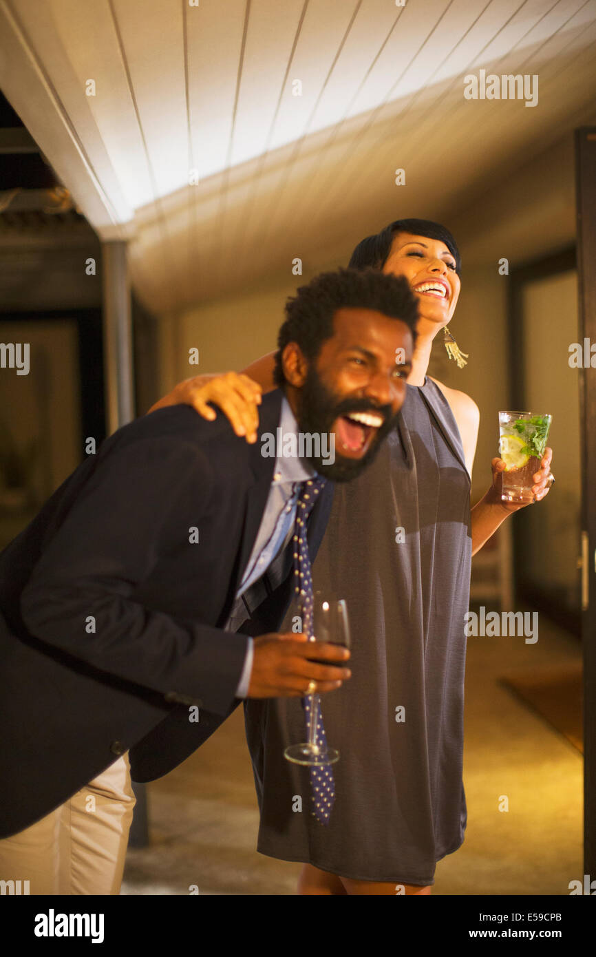 Couple laughing together at party Banque D'Images