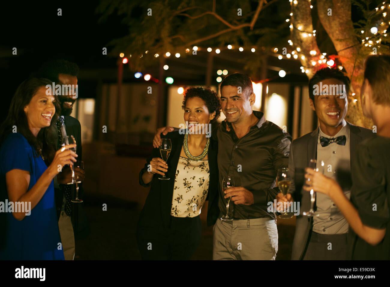 Les amis rient ensemble at party Photo Stock