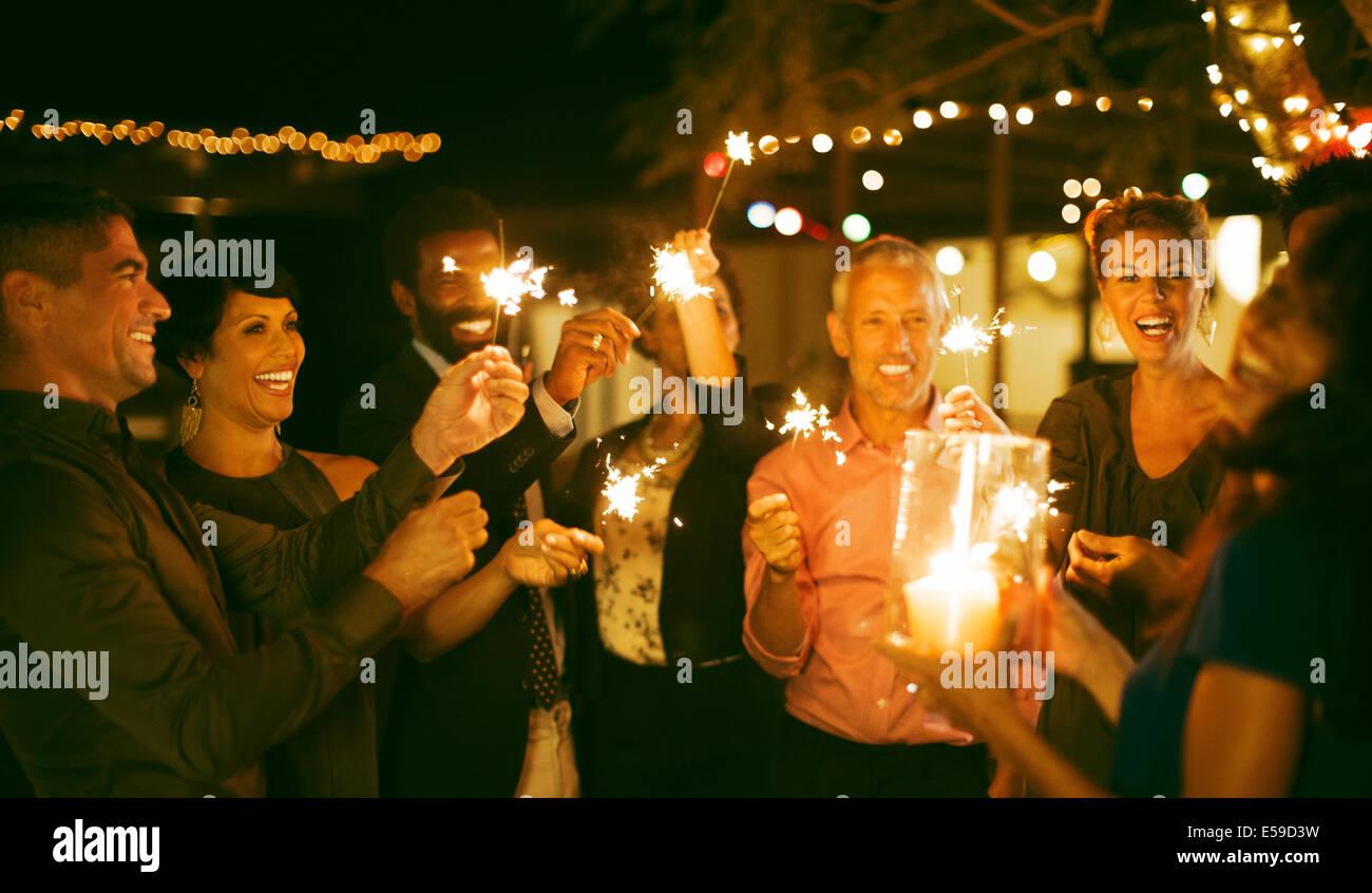 Amis jouant avec les étinceleurs at party Photo Stock