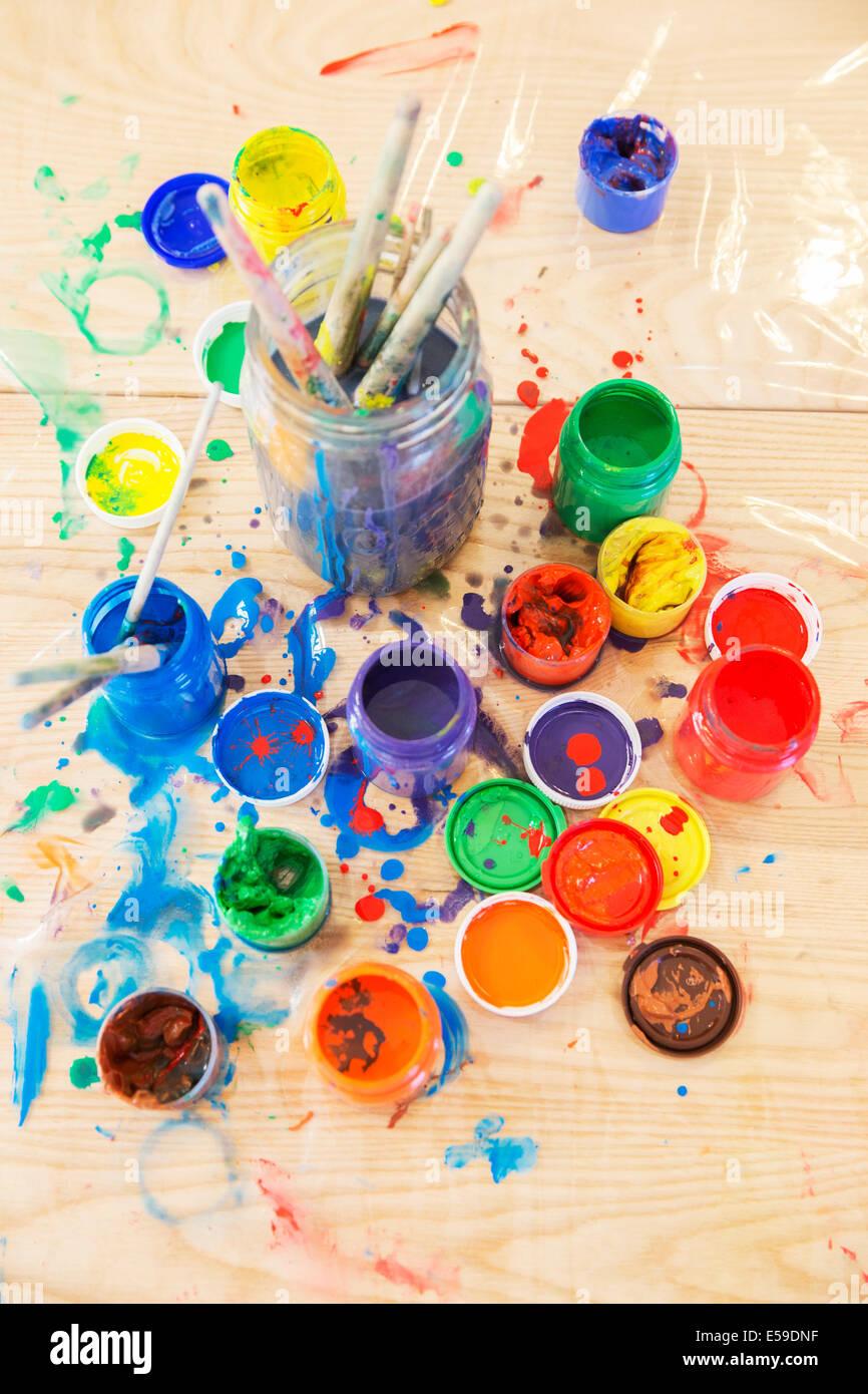 Pots de peinture et pinceaux sur table en bois Photo Stock