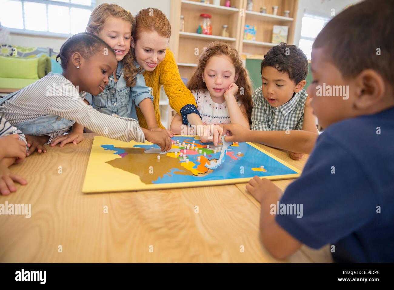 Les enfants et l'enseignant jouant dans la classe Photo Stock