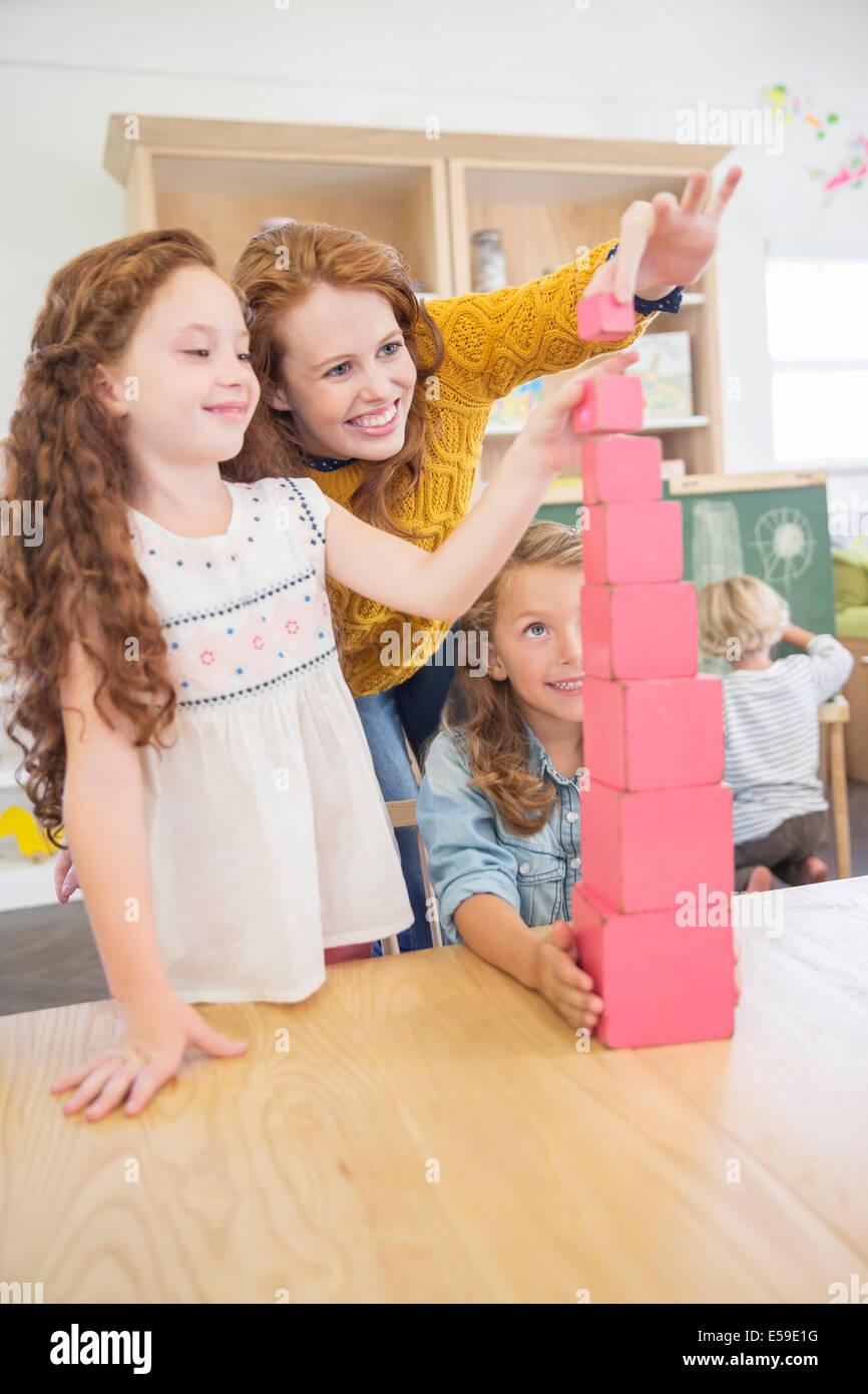 Les élèves et l'enseignant en classe dans des blocs d'empilage Photo Stock
