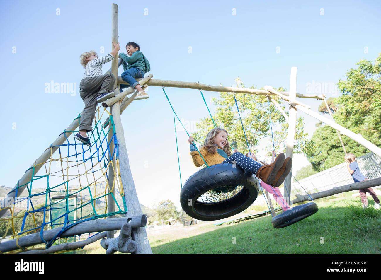 Les enfants jouant sur les structures de jeu Photo Stock