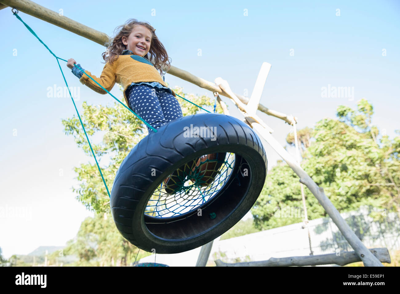Girl playing on tire swing Photo Stock