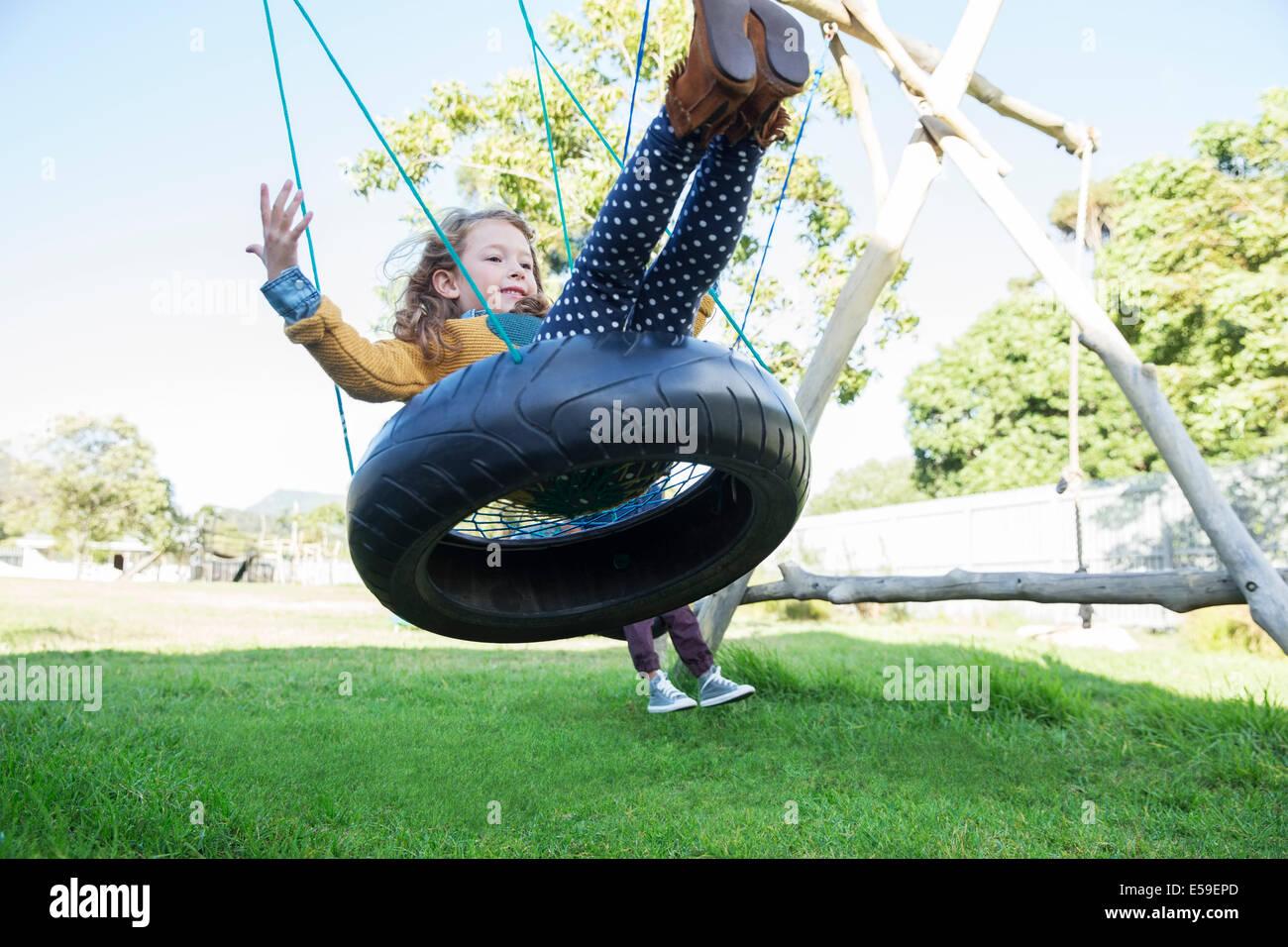 Les enfants jouant sur les balançoires pneu Photo Stock