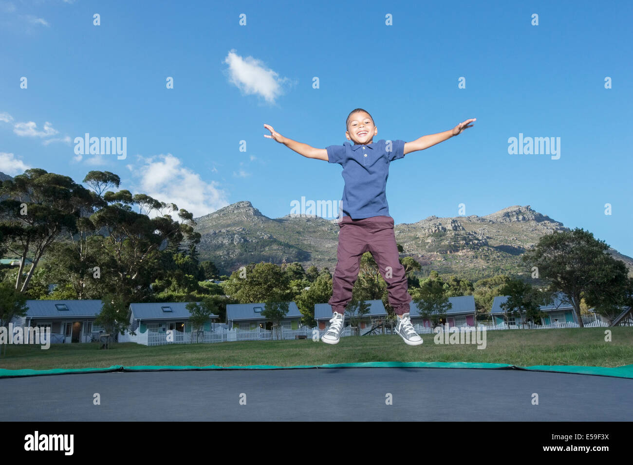 Garçon sautant sur le trampoline à l'extérieur Photo Stock