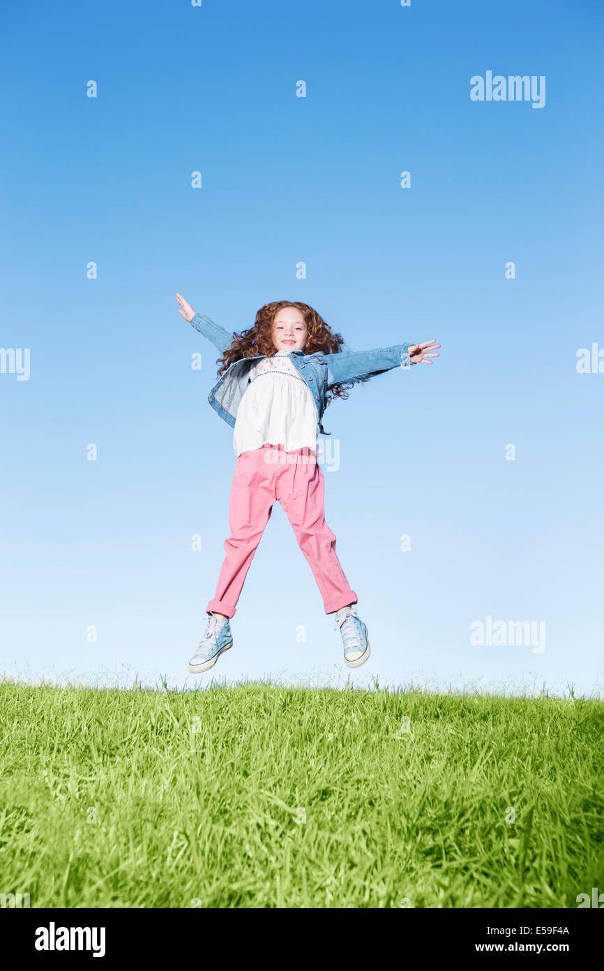 Girl jumping for joy on grassy hill Photo Stock