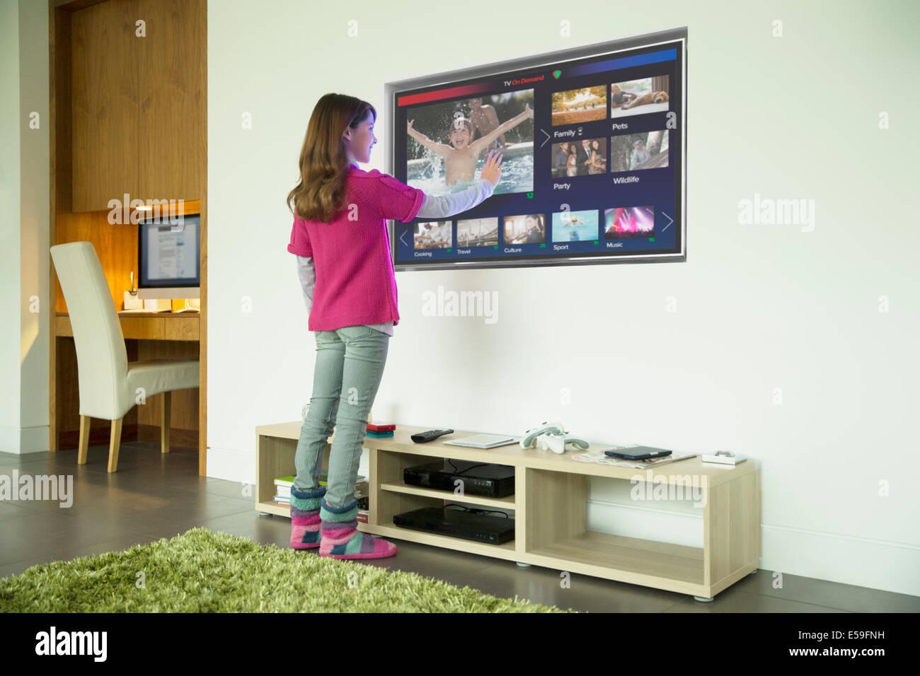 Fille à l'aide d'un écran tactile dans le salon de télévision Photo Stock