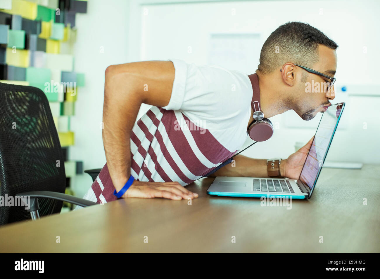 Man kissing laptop in office Photo Stock