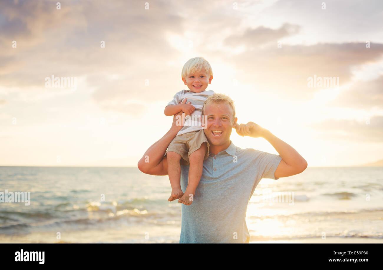 Fils Père tient sur ses épaules sur la plage au coucher du soleil. Photo Stock
