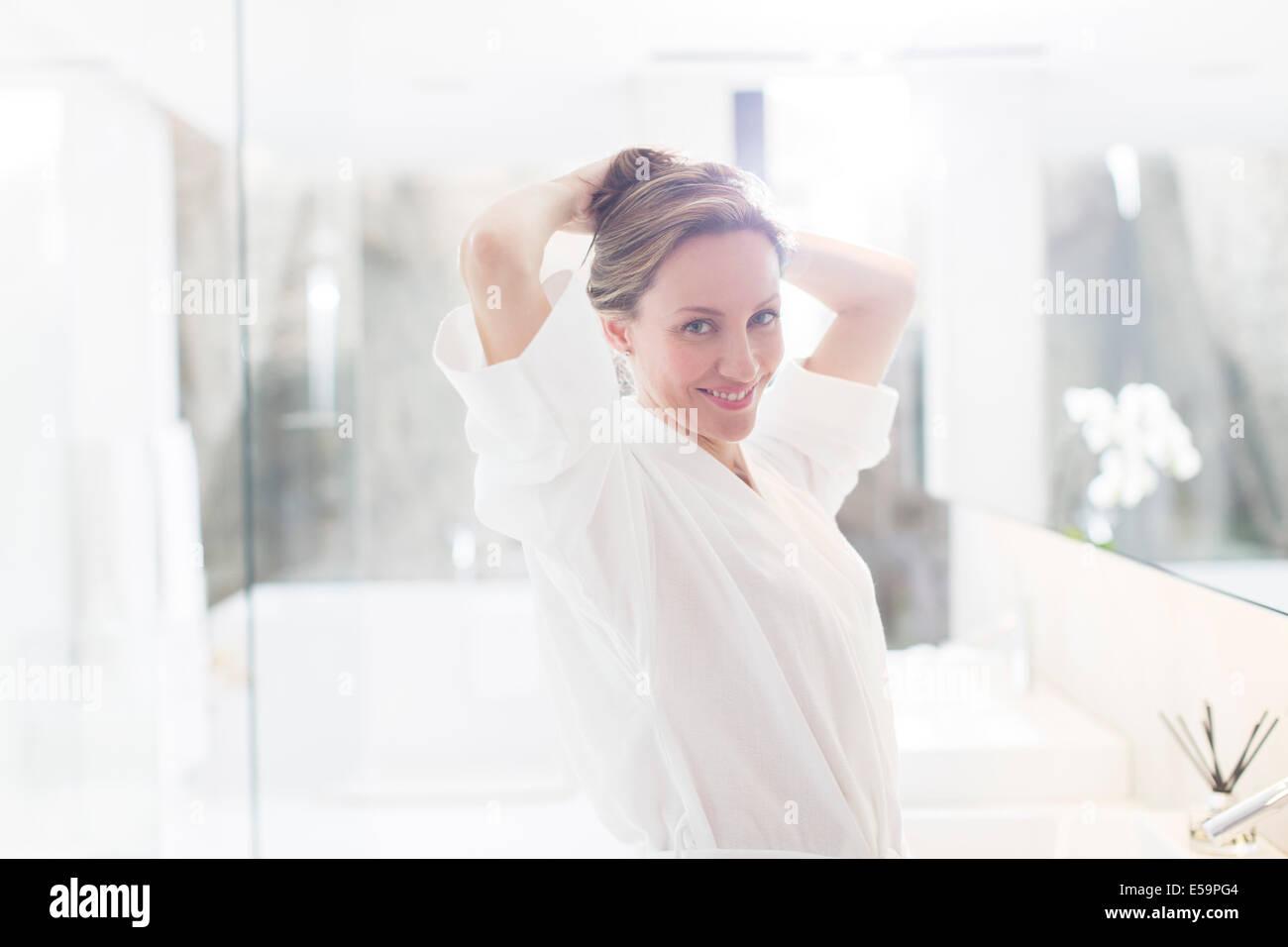 Woman putting up ses cheveux dans la salle de bains Photo Stock