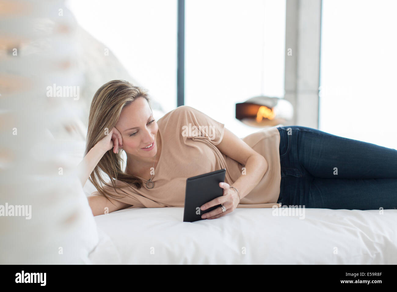 Woman using digital tablet on bed Photo Stock