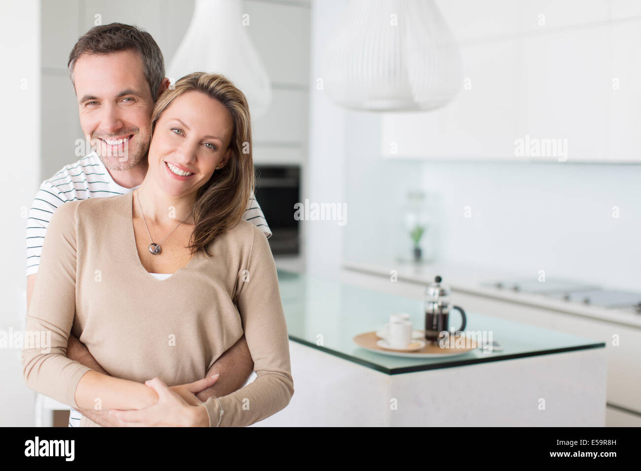 Couple hugging in modern kitchen Photo Stock