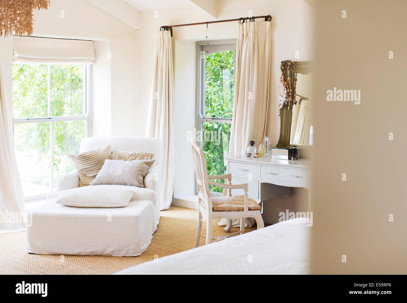 Fauteuil et vanité dans chambre à coucher rustique Photo Stock