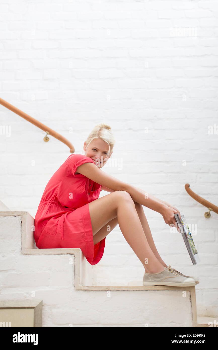 Femme assise sur les marches de la maison moderne Photo Stock