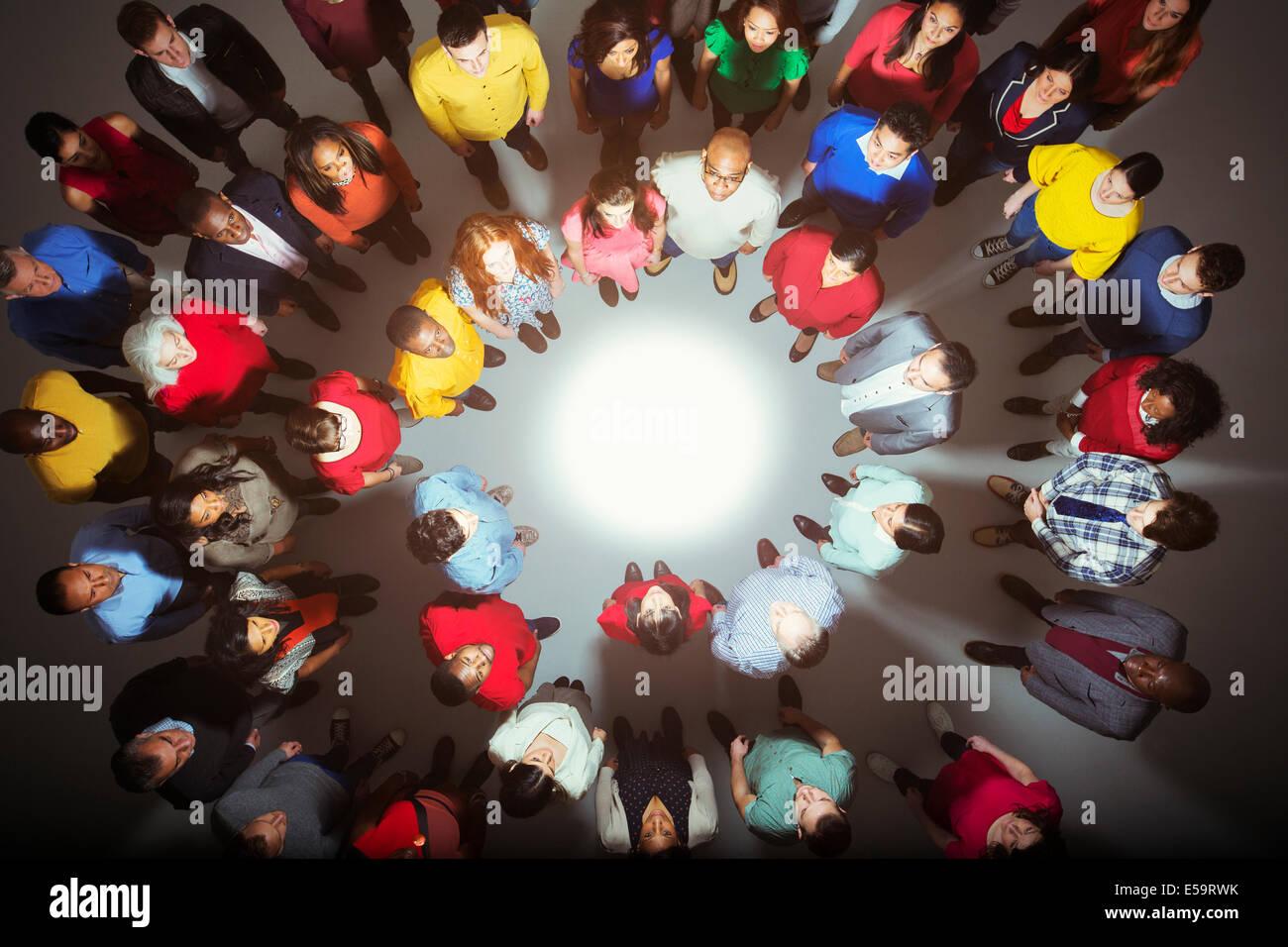 Foule diversifiée debout autour d'une lumière vive Photo Stock