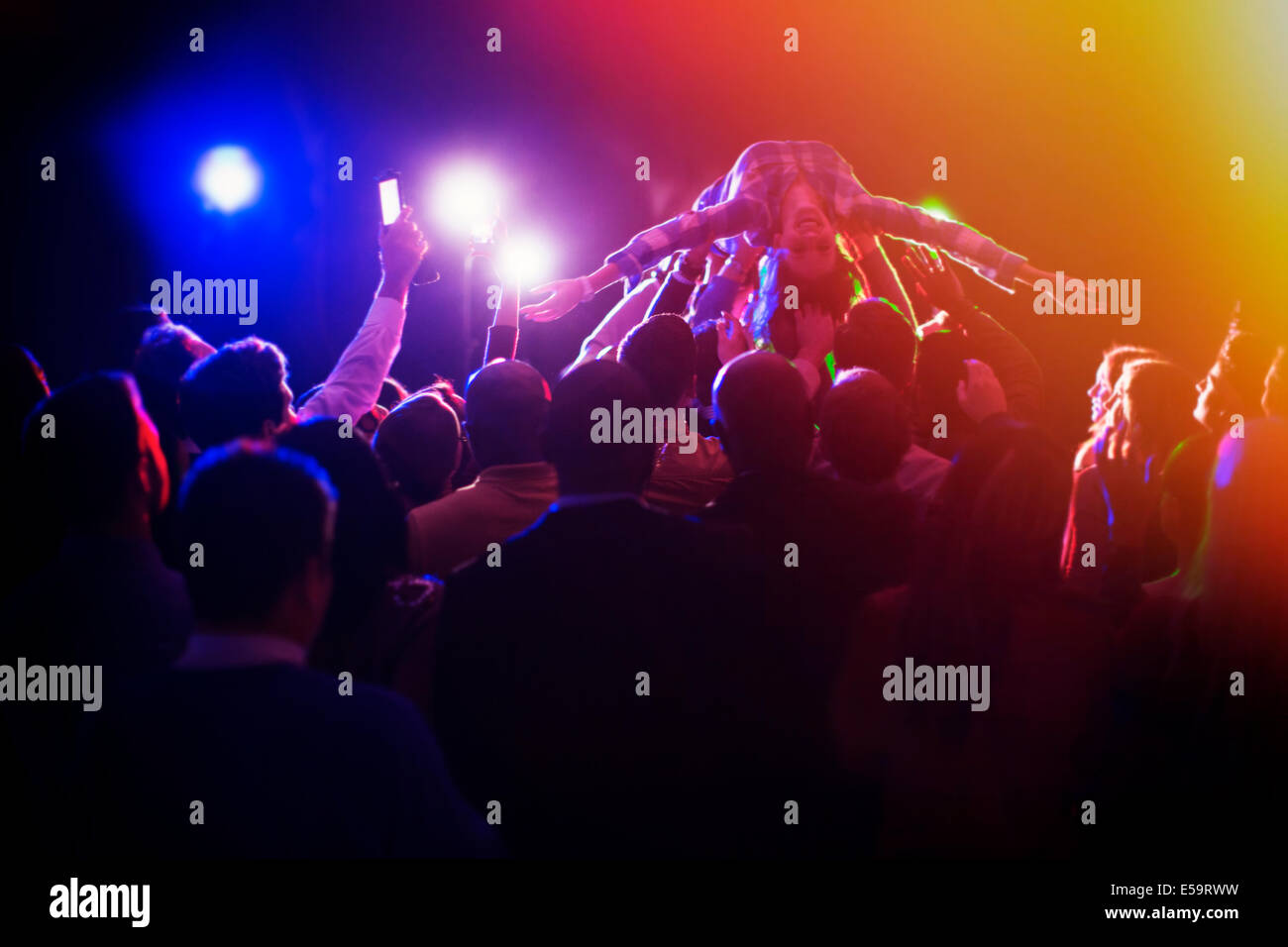 Woman crowd surfing au concert Photo Stock
