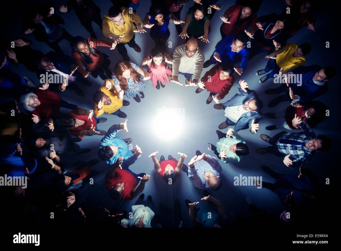 Les gens d'affaires faisant cercle autour de la lumière vive Banque D'Images