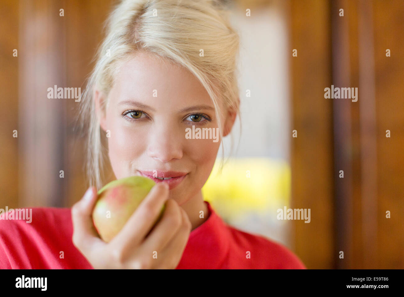 Woman eating apple à l'intérieur Photo Stock