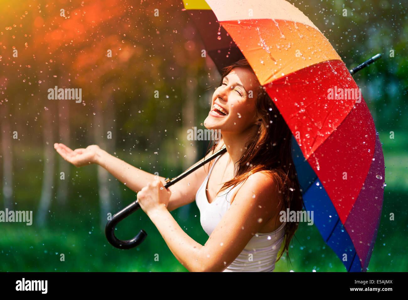 Laughing woman with umbrella contrôler pour la pluie, Debica, Pologne Banque D'Images