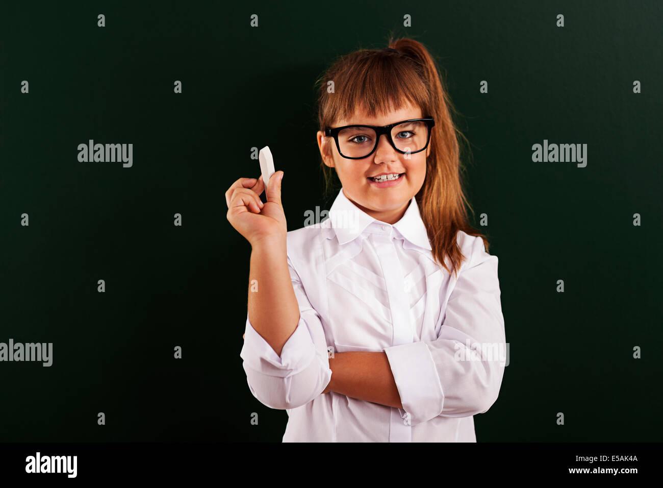 Cute little girl dans les verres avec de la craie en main, Debica, Pologne. Photo Stock