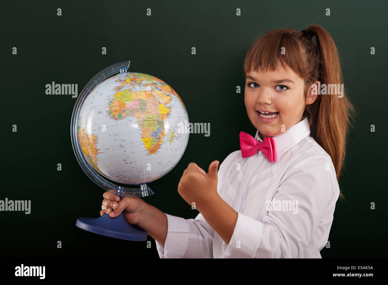 Écolière avec globe showing ok sign, Debica, Pologne. Photo Stock