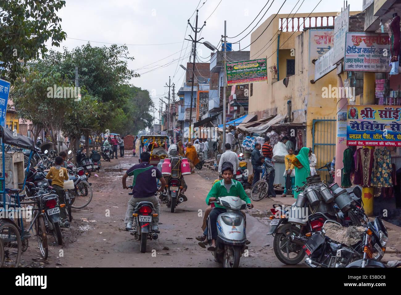 Le trafic lourd dans rue latérale, avec quelques petits magasins et où le lait est livré en moto. Photo Stock