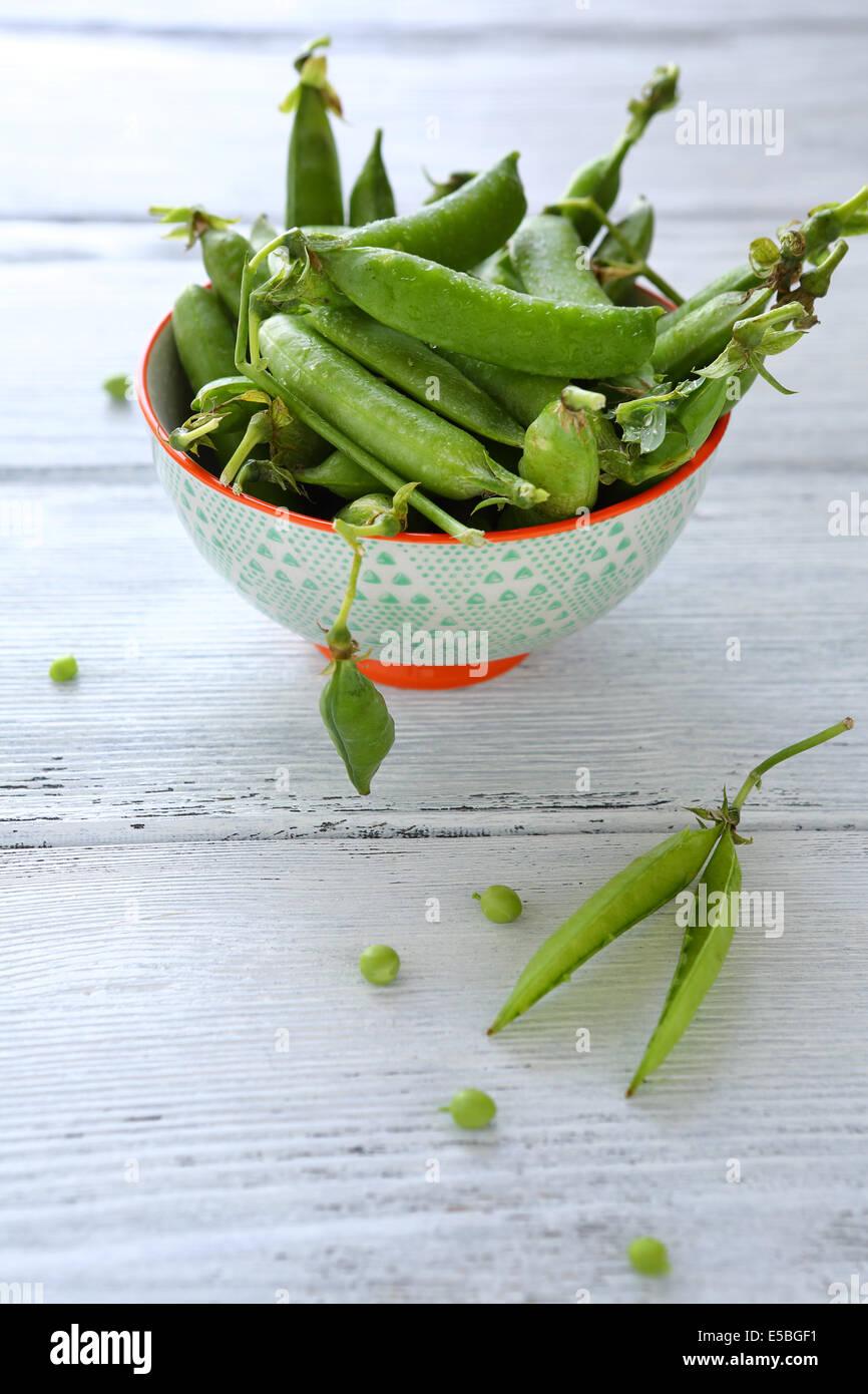 Petits pois dans un bol blanc, gros plan de l'alimentation Photo Stock