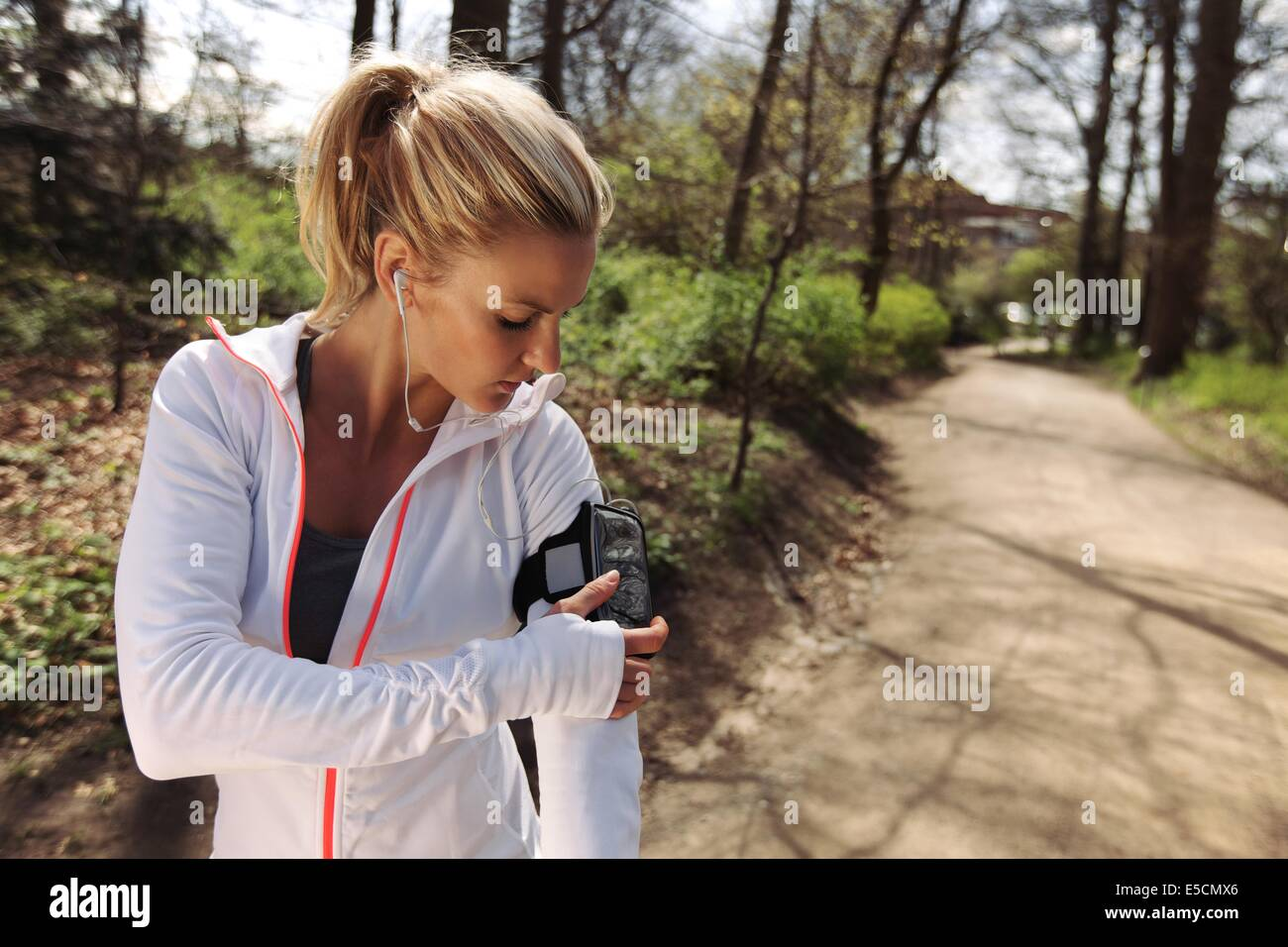 Belle jeune femme de la formation à l'extérieur pendant qu'à l'aide d'un smartphone Photo Stock