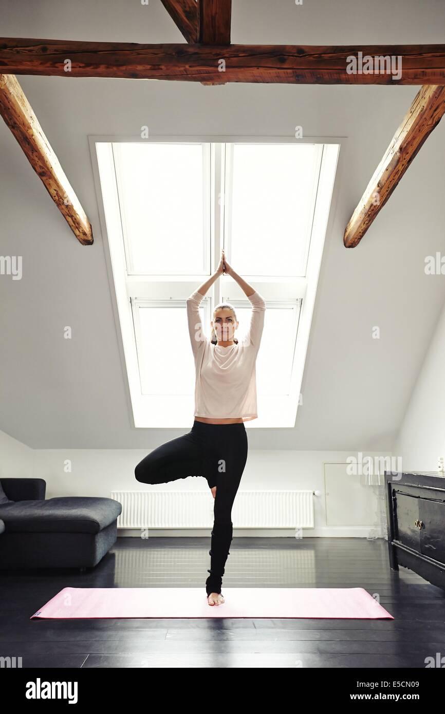 Jeune femme pratiquant le yoga dans la salle de séjour. Femelle en bonne santé debout sur une jambe et la méditation à la maison. Mettre en place des femmes en posture de l'arbre d Banque D'Images
