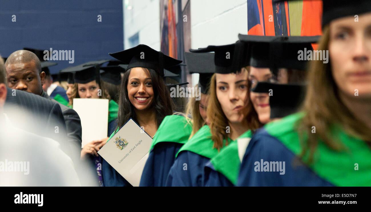 Une jeune femme sur son jour de graduation habillé en robe et chapeau, conseil de mortier tenant son degré Photo Stock