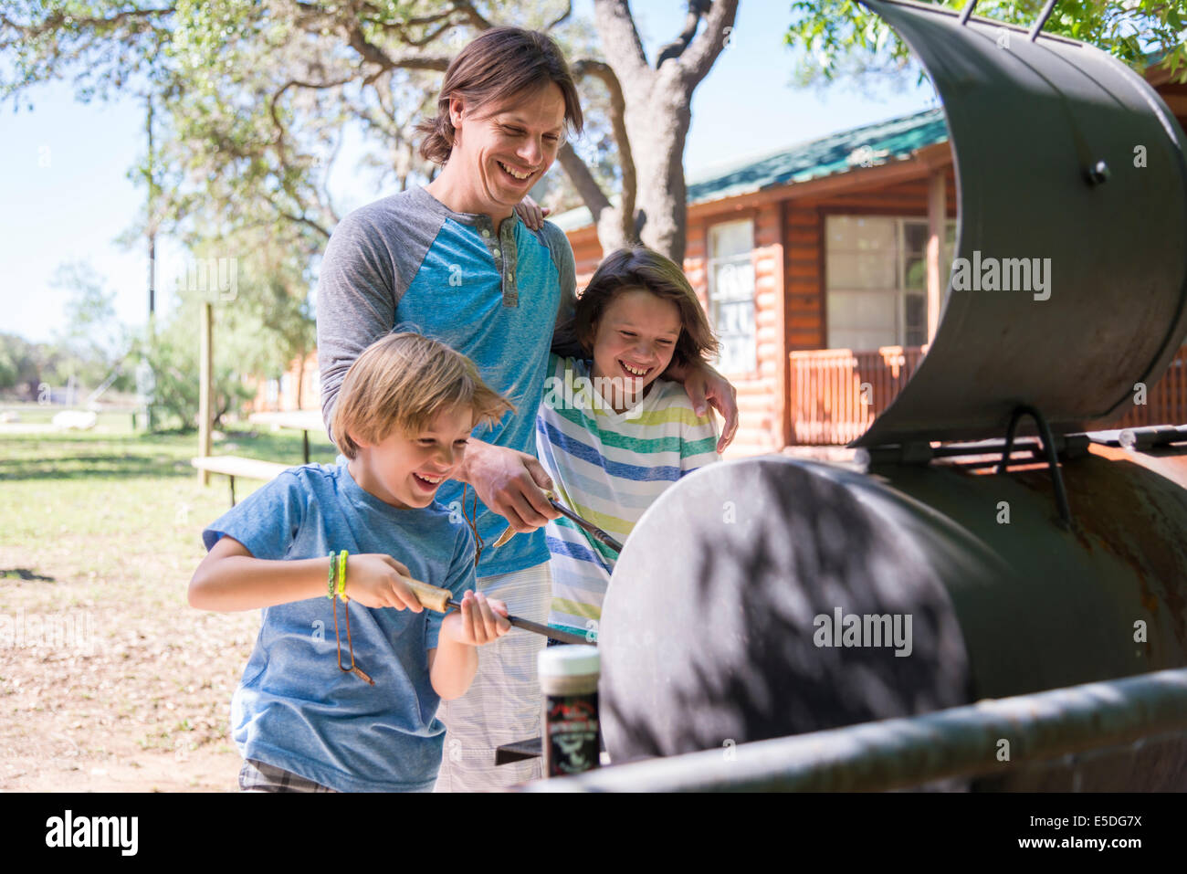 USA, Texas, père de deux fils s'amusant à barbecue Photo Stock