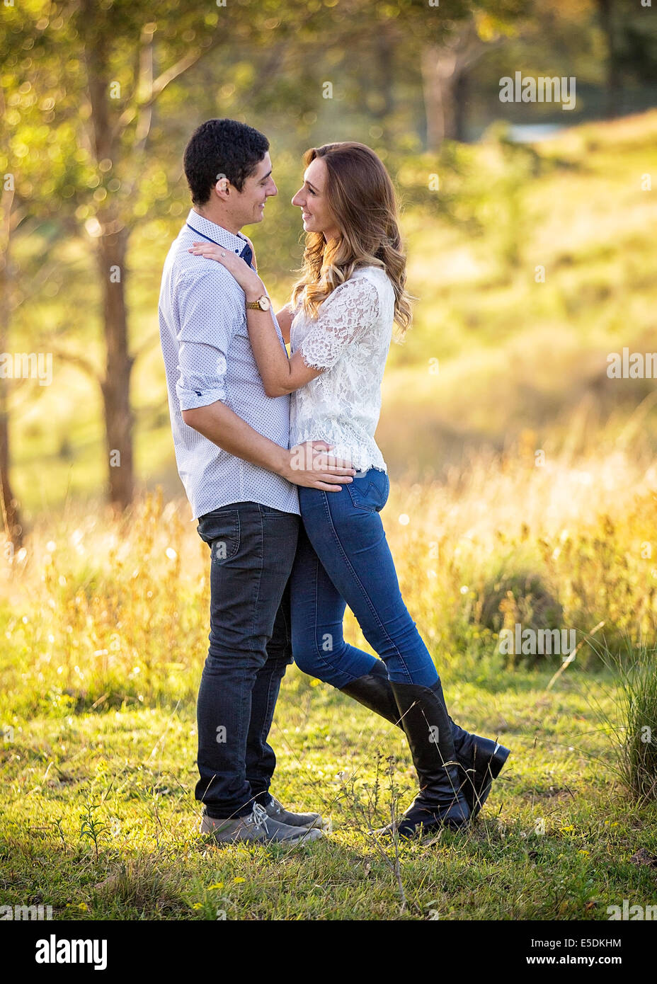 Jeune couple standing in embrasser dans un cadre rural Photo Stock