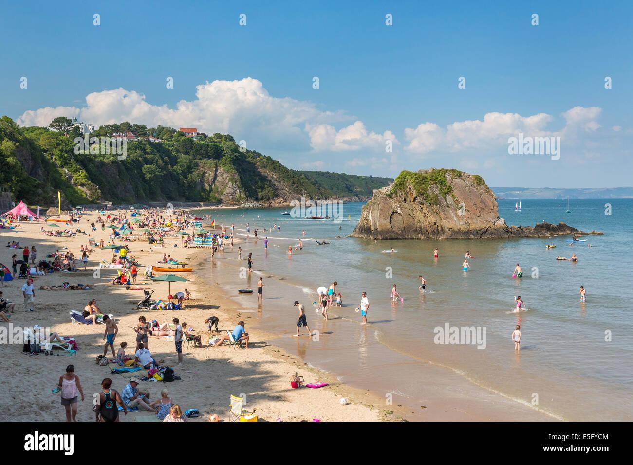 Plage du Nord à Tenby plein de vacanciers - photographiée avec Goscar Rock. Tourisme au Pays de Galles Photo Stock