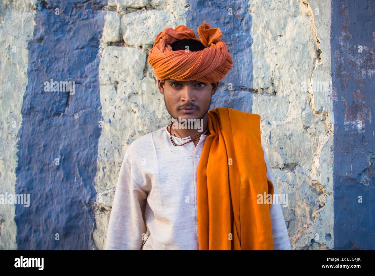 Jeune homme hindou coloré, portant un turban orange, posant devant un mur dans la partie ancienne de New Delhi, Photo Stock