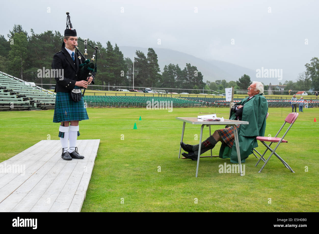 Piper et juge à la concurrence à la tuyauterie Solo Junior Braemar Highland Games en juillet en Ecosse, Photo Stock