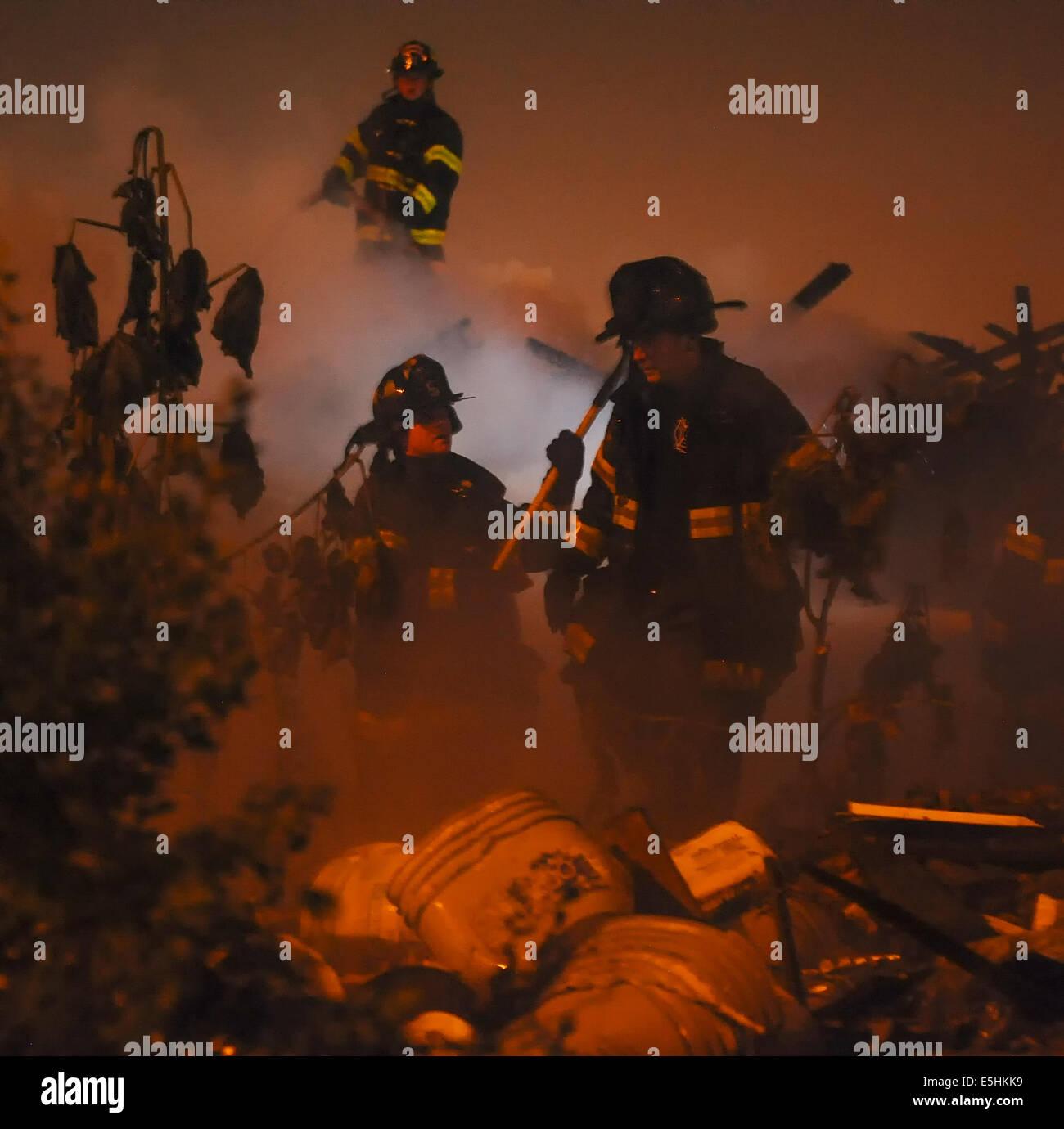 Les pompiers d'évaluer les dégâts d'un tas d'ordure fire à Baltimore avant la remise Photo Stock