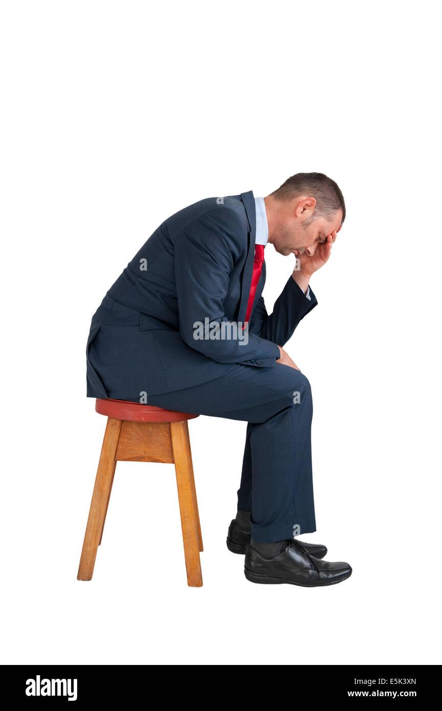 Homme déprimé assis isolé sur fond blanc Photo Stock