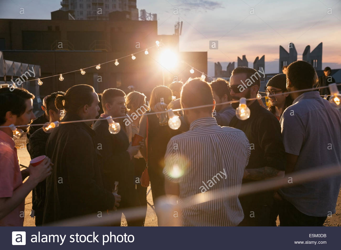 String lights sur crowd at rooftop party Photo Stock