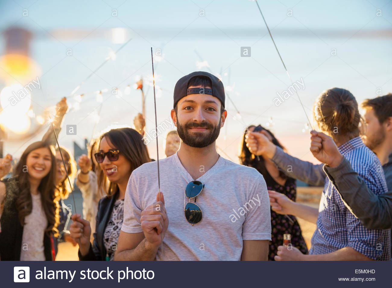 Portrait of smiling man with sparkler at party Photo Stock