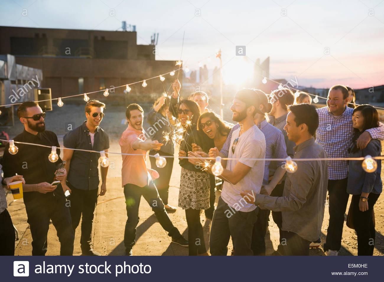 Amis avec les étinceleurs bénéficiant d'urban rooftop party Photo Stock