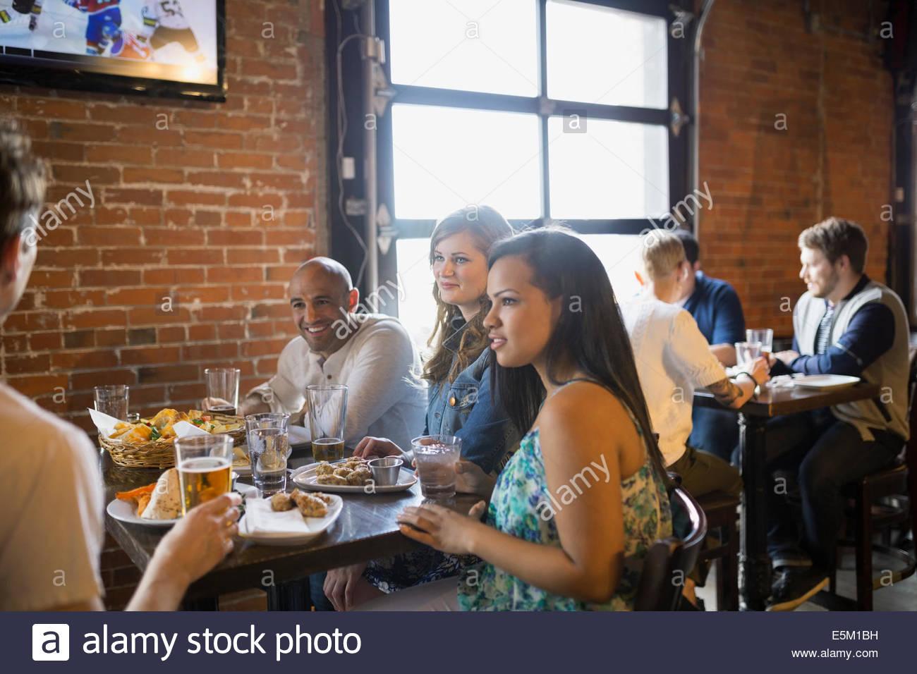 Les amis de parler et de manger en pub Photo Stock