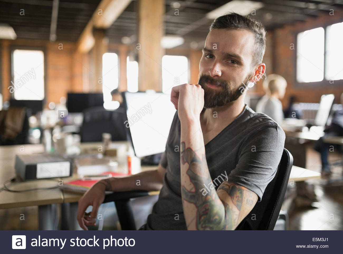 Portrait of smiling businessman with tattoos in office Photo Stock