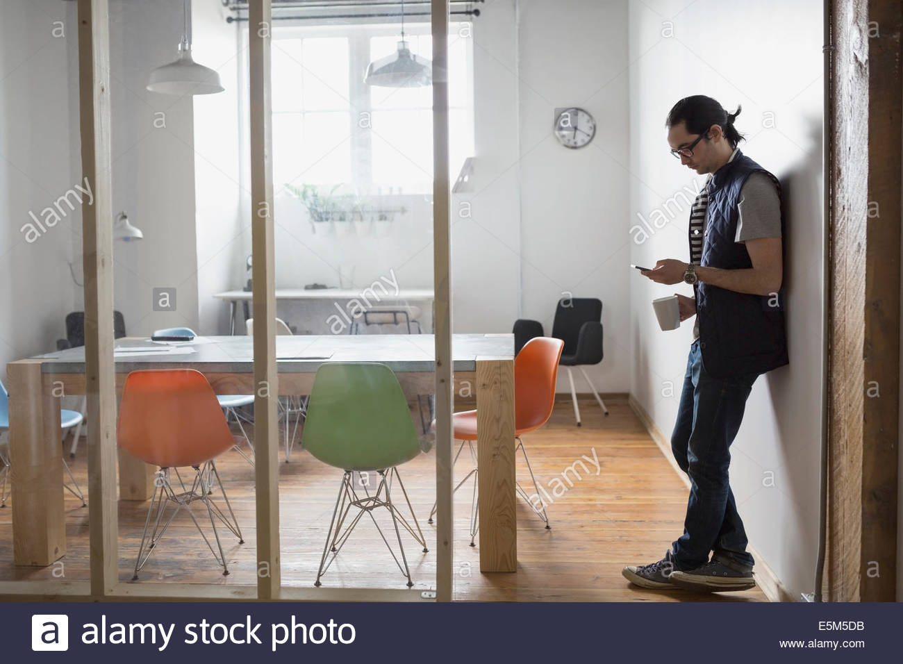 Businessman using cell phone in conference room Photo Stock